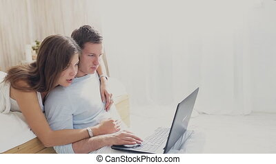 loving couple with laptop at home