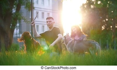 Loving couple with their dogs having a rest outdoors -...