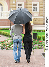 Loving couple with umbrella. Rear view of young couple walking on street while man holding umbrella