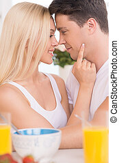 Loving couple. Young loving couple looking at each other while having breakfast together