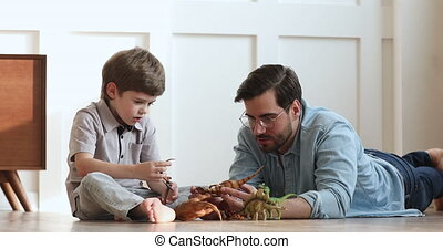 Loving dad and preschool child son playing dinosaurs at home...