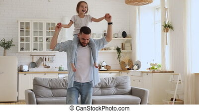 Loving dad carrying kid daughter giving piggyback ride at home