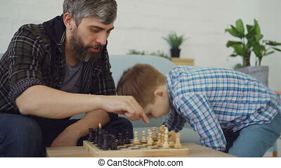 Loving dad is playing chess with his little child, teaching...