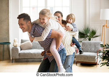 Loving dad piggybacking little daughter playing with family at h