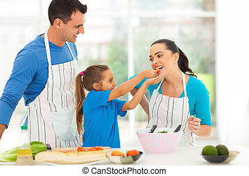 loving daughter feeding mother a piece of tomato
