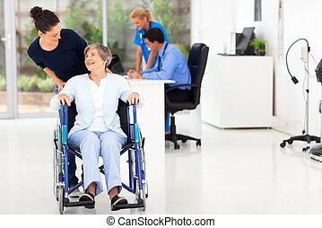 loving daughter taking senior mother visit doctor