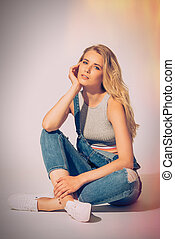 Loving denim. Studio shot of beautiful young woman in jeans overall looking at camera while sitting on the floor