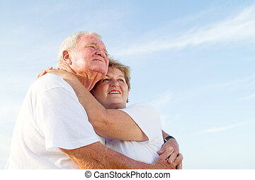 loving elderly couple on beach hugging and smiling against a...