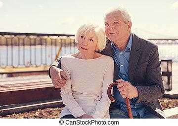 Loving elderly couple sitting together on the bridge