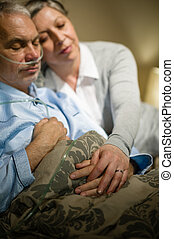 Loving elderly couple sleeping in bed