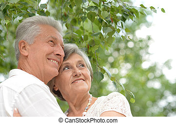 loving elderly couple on a walk in the park in summer