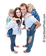 Loving family enjoying piggyback ride against a white ...