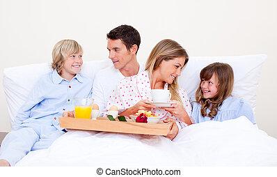 Loving family having breakfast sitting on bed