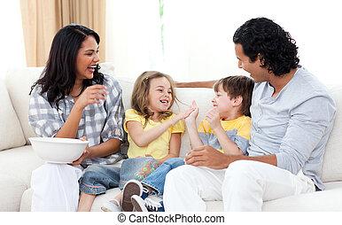 Loving family watching TV on sofa