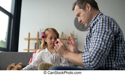 Loving father adjusting hair rollers on the hair of his nice little daughter