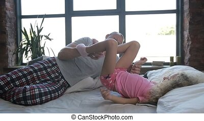 Loving father and cute daughter playing in bed