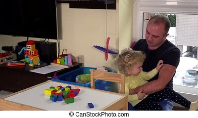 Loving father combing her daughter girl hair with brush at home