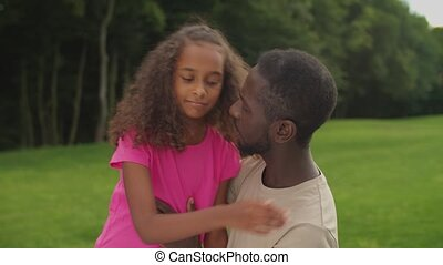 Affectionate handsome african father comforting his cute sad elementary age mixed race daughter with curly hair in summer nature, expressing love, care, support and encouragement.