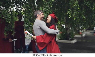 Loving father is congratulating his daughter on graduation...