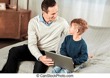 Joyful nice man looking at his son