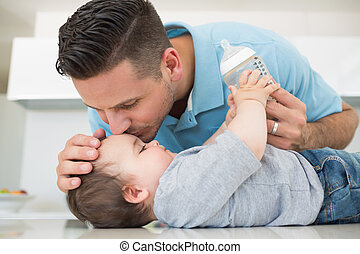 Loving father kissing baby boy on f