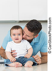 Loving father kissing baby sitting on counter