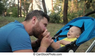Loving father kissing feet of his baby son in park
