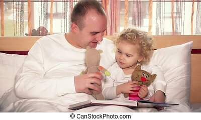 Loving father playing with her toddler daughter girl using toy cats