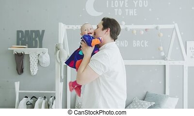 Loving father playing with joyful baby at home