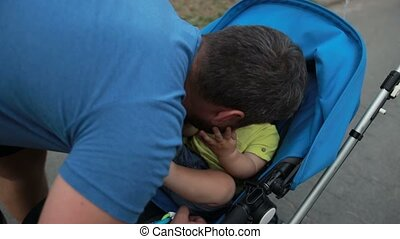 Loving father playing with toddler son in stroller