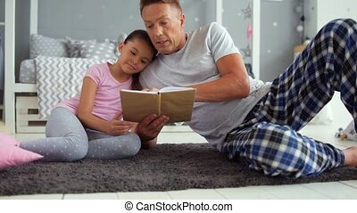 Loving father reading books with his little daugher