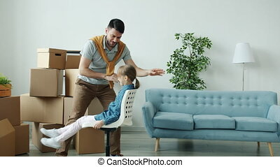 Loving father is riding chairs with cute little daughter then hugging kissing expressing love in new apartment during relocation. People and children concept.