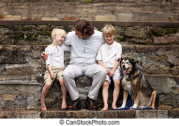 Loving Father Sitting with his two Happy Children and Their Pet Dog on Summer Day
