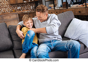 Loving father tickling his little son on sofa - Happy ...