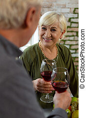 Loving female looking at husband and holding glass of wine