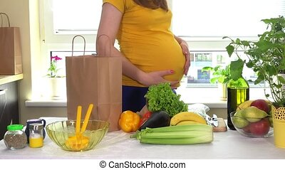 Loving future mother caress tender belly near kitchen table full of organic food