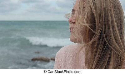 Loving girl enjoying the coolness of sea breeze - Happy...