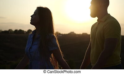 Loving girl in a dress and a guy hold hands and flirt in slow motion during sunset on the field. Happy and lovely relationship of young people. A date on the field of a young couple, close-up view.