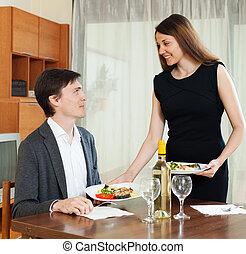Loving girl serving dinner to beloved man at table