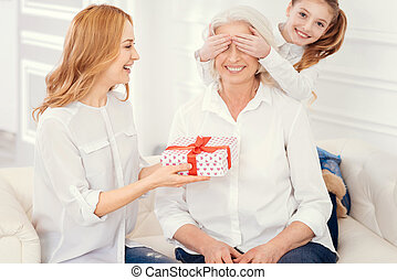 Loving grandchild and mom making surprise gift for grandmother