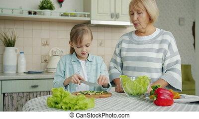 Loving grandchild cutting cucumbers making salad and feeding...