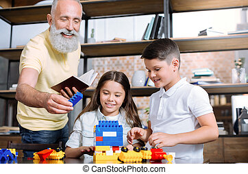 Loving grandfather helping kids with house construction