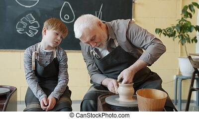 Loving grandfather making ceramic pot on throwing wheel and ...