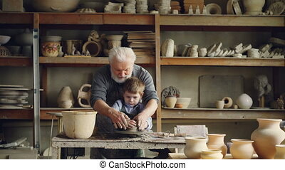 Loving grandfather professional potter is teaching his small grandchild to mold clay on potter's wheel. Little boy is laughing and enjoying new hobby.
