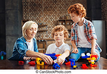 Loving grandmother playing with kids at home