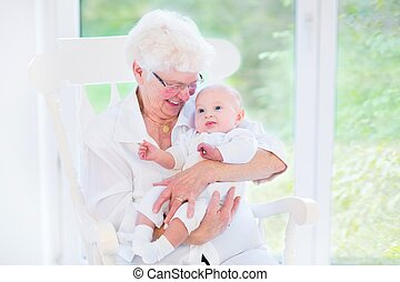 Loving grandmother singing a song to her newborn baby grandson