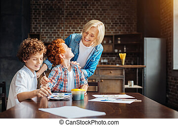 Loving granny looking and grandchildren painting together -...