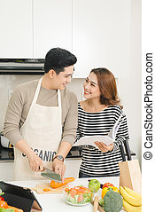 Loving happy couple preparing a healthy salad of fresh vegetables in the kitchen
