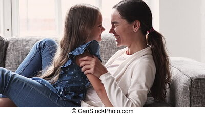 Loving happy mixed race mother lying on comfortable couch, having fun with laughing cute child daughter at home. Smiling 2 different female generations family enjoying playtime on weekend indoors.