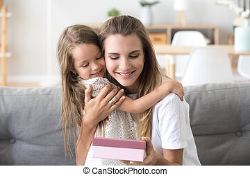 Loving happy mother embracing, thanking little daughter for present